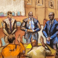 R. Kelly stands alongside lawyers Nicole Blank Becker, Thomas Farinella and Calvin Scholar while jurors raise their hands to take the oath as jury selection begins for Kelly's sexual abuse trial in Brooklyn, August 9, 2021. Reuters/Jane Rosenberg